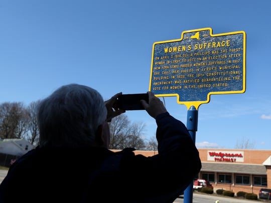 Sid Barefoot of Le Roy takes a photo of the marker in honor of Delia Phillips who became the first woman in Le Roy to vote, 100 years ago. The marker was placed at the Le Roy Municipal Building during a ceremony on April 2, 2018.