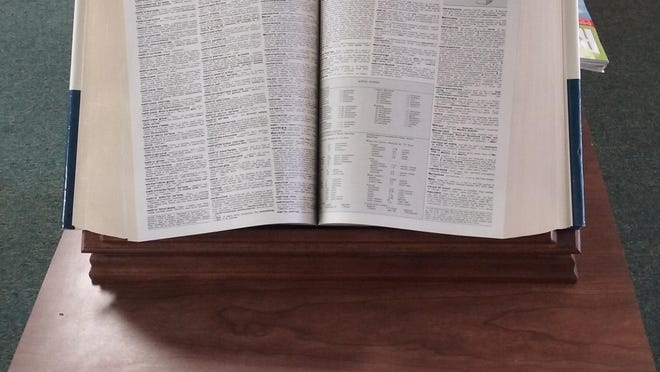 A large dictionary occupies a place of honor in a Library.