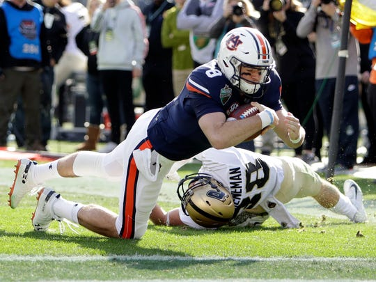 Auburn quarterback Jarrett Stidham (8) drives past Purdue safety Brennan Thieneman (38) and into the end zone in the first half of the Music City Bowl NCAA college football game Friday, Dec. 28, 2018, in Nashville, Tenn. Stidham was ruled down at the 1-yard line. (AP Photo/Mark Humphrey)