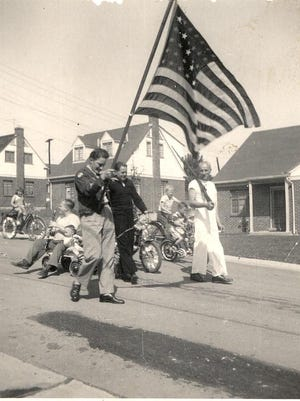 Jack Strassel carries a flag as Walter Bricking in a U.S. Navy uniform pulls a wagon carrying Bill Bunge as Bill Slaline carries a rifle at right during the City of Crestview's first Memorial Day parade in 1948 when the city was named Vet Village.