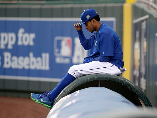 Kansas City Royals starting pitcher Yordano Ventura sits on the tarp as he watches a baseball workout Sunday, Oct. 25, 2015, in Kansas City, Mo. The Royals will face the New York Mets in Game 1 of the World Series on Tuesday in Kansas City. (A (AP Photo/Charlie Riedel)