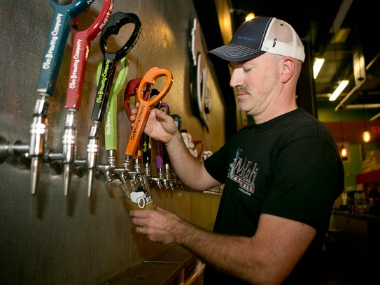 O'so Brewing Company president Marc Buttera pours beer