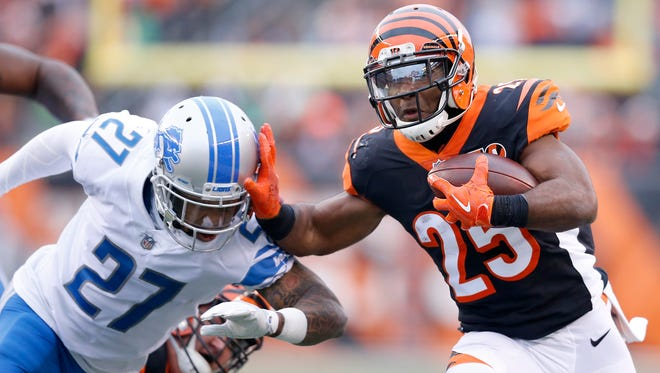 Cincinnati Bengals running back Giovani Bernard (25) stiff arms Detroit Lions free safety Glover Quin (27) on a carry in the second quarter of the NFL Week 15 game between the Cincinnati Bengals and the Detroit Lions at Paul Brown Stadium in downtown Cincinnati on Sunday, Dec. 24, 2017. At halftime the Bengals trailed 7-6.