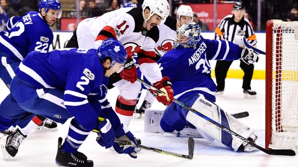 Toronto Maple Leafs goalie Frederik Andersen (31) stretches to make a save as New Jersey Devils center Brian Boyle (11) and Maple Leafs defenseman Ron Hainsey (2) look for a rebound during first period NHL hockey action, in Toronto on Thursday, Nov. 16, 2017. THE CANADIAN PRESS/Frank Gunn/The Canadian Press via AP)