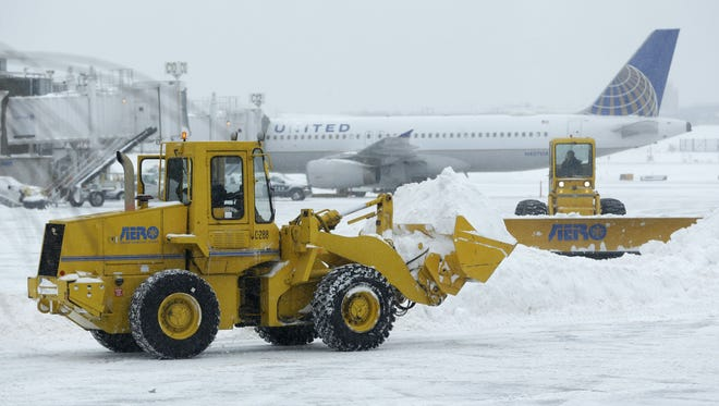 Machines clear snow off the tarmac at LaGuardia Airport in New York on Jan. 27, 2015.