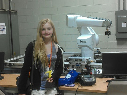 While attending a Women in Technology program at Lake Superior State University, Olivia Dahl wowed her instructors by using a 3-D printer to create the model she is holding of the device behind her.