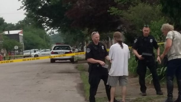 Detectives with Evansville Police Department talk to witnesses at the scene of a shooting that occurred in the 1100 block of West Delaware Street Friday evening.
