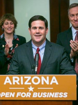 Arizona Governor Doug Ducey announces a $2 billion Mesa Apple command center at the Arizona State Capital in Phoenix on Monday, February 2, 2015. Behind him are Sandra Watson, Arizona Commerce Authority CEO, and Mesa Mayor John Giles.