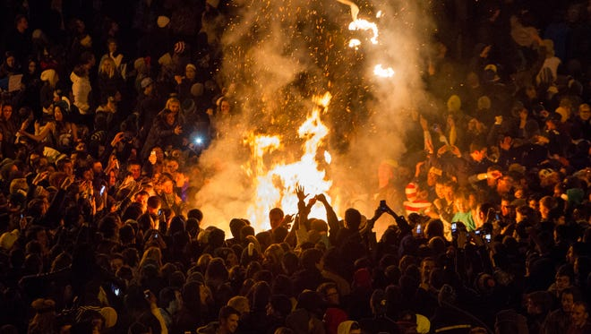 Unruly Michigan State fans celebrate the Spartans' win against Ohio State early Sunday in East Lansing's Cedar Village.  Thousands of students celebrated the team's Big Ten title with large, rowdy bonfires.