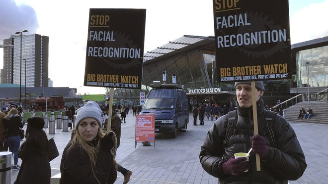 FILE - In this Feb. 11, 2020, file photo, Silkie Carlo, left, demonstrates in front of a mobile police facial recognition facility outside a shopping centre in London. A Black man who says he was unjustly arrested because facial recognition technology mistakenly identified him as a suspected shoplifter is calling for a public apology from Detroit police. And for the department to abandon its use of the controversial technology.