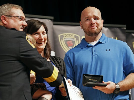 Retired Springfield police officer Aaron Pearson (with his wife, Amanda) receives a Purple Heart from Police Chief Paul Williams in 2015.