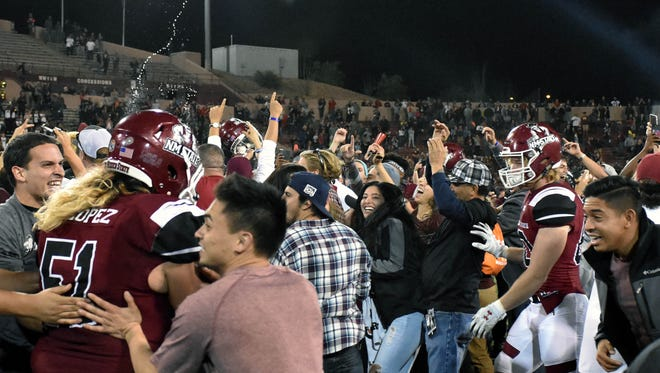Aggie fans and players celebrate on the field after the game.