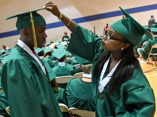 Graduate Martenae' Wright helps classmate Timothy Wells