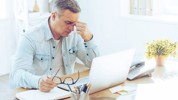 Frustrated older man looking at computer
