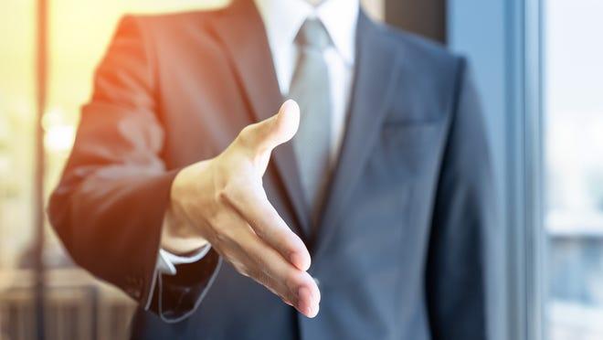 Man in suit extending handshake