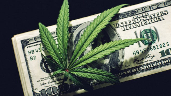 A cannabis leaf laid atop a small stack of one hundred dollar bills.