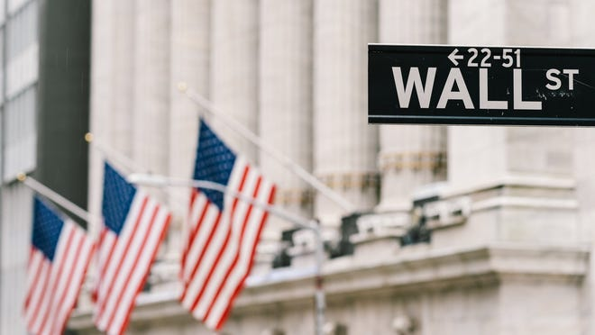 Wall Street sign with U.S. flags in front of the New York Stock Exchange in background