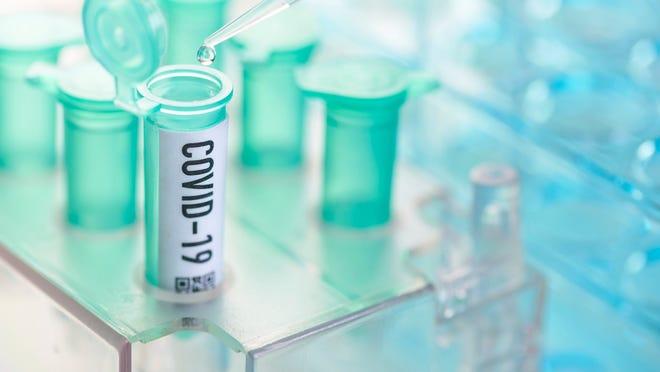 Pipette pouring liquid into a COVID-19 test tube in a lab.
