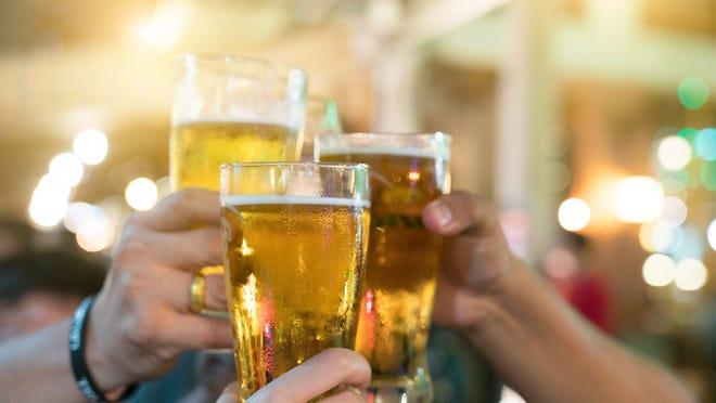 Three beer drinkers clink their glasses.