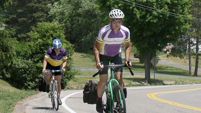 Dan Manglapus, left, and Brian Heppard head up Hickory Grove Road in Horseheads on their way to Corning on Monday afternoon. The two cyclists are raising money during a six-day bike tour through the nine counties served by the Rochester and Finger Lakes Alzheimer Association Chapter.