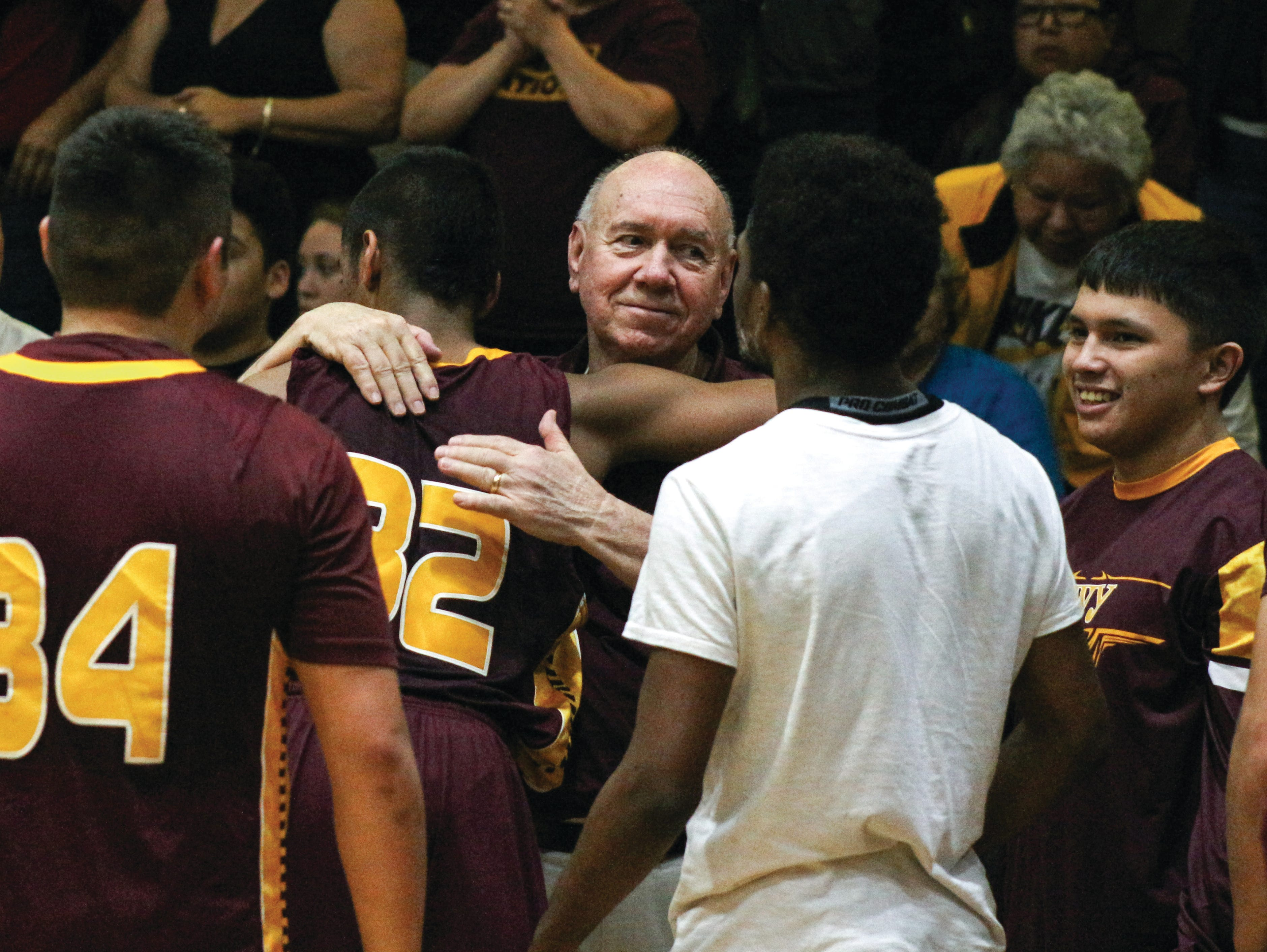 Former Cherokee boys basketball coach Willis Tullos is congratulated by his players after winning his 600th career game in January.