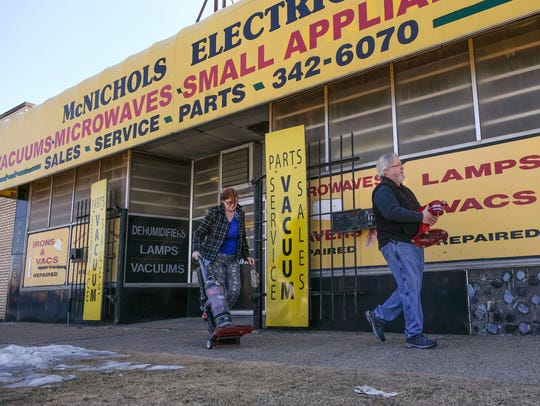 McNichols Electric co-owner Pat Kehoe helps carry a