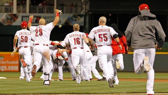 The Reds mob catcher Devin Mesoraco at second base after his game-winning double May 12 against the Braves.