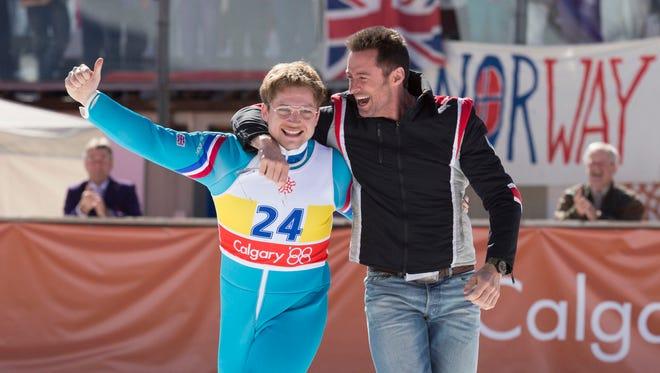 "Eddie (Taron Egerton) and his coach Bronson Peary (Hugh Jackman) rejoice in Eddie's triumph in ""Eddie the Eagle."""