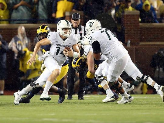 Michigan State quarterback Brian Lewerke scrambles