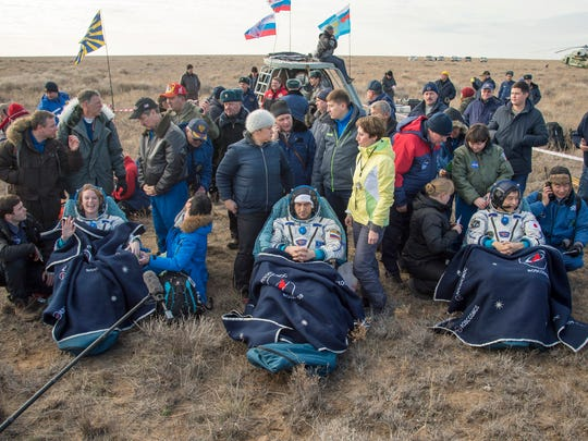 NASA astronaut Kate Rubins, left, Russian cosmonaut Anatoly Ivanishin, center, of Roscosmos and astronaut Takuya Onishi of the Japan Aerospace Exploration Agency (JAXA) sit in chairs outside the Soyuz MS-01 spacecraft just minutes after they landed in a remote area near the town of Zhezkazgan, Kazakhstan Sunday, Oct. 30, 2016. The Russian Soyuz space capsule has landed in Kazakhstan, bringing back three astronauts from the United States, Japan and Russia back to Earth from a 115-day mission aboard the International Space Station.