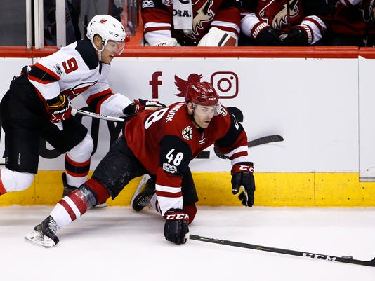 Arizona Coyotes left wing Jordan Martinook (48) falls to the ice as he tries to keep the puck away from New Jersey Devils left wing Taylor Hall (9) during the second period of an NHL hockey game Saturday, March 11, 2017, in Glendale, Ariz. (AP Photo/Ross D. Franklin)