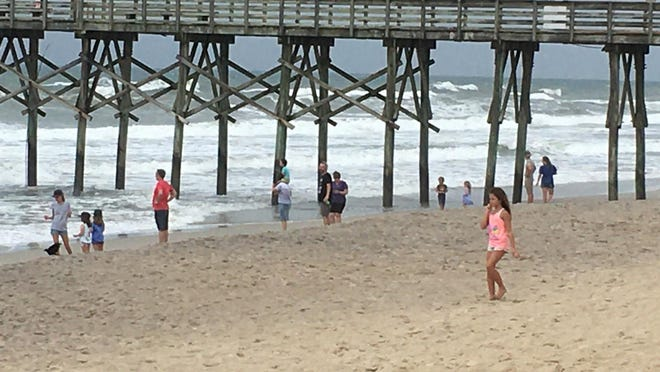 People gathered near the Surf City Pier on Topsail Island in Pender County on Monday afternoon, Aug. 3, as Tropical Storm Isaias approached Southeastern N.C.