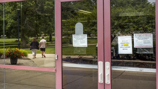 Light foot traffic on the Bradley University campus as reflected in the glass of the library building Monday, June29, 2020.