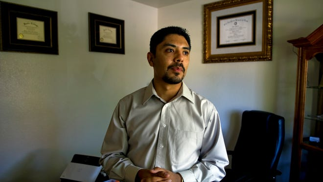 Sergio Garcia stands in his California home office with his degrees from California Northern School of Law, at right,  and two degrees from Butte Community College; one for social and behavioral science and the other for business administration. Sergio Garcia's family illegally crossed into the U.S. from Mexico when he was 17 months old.