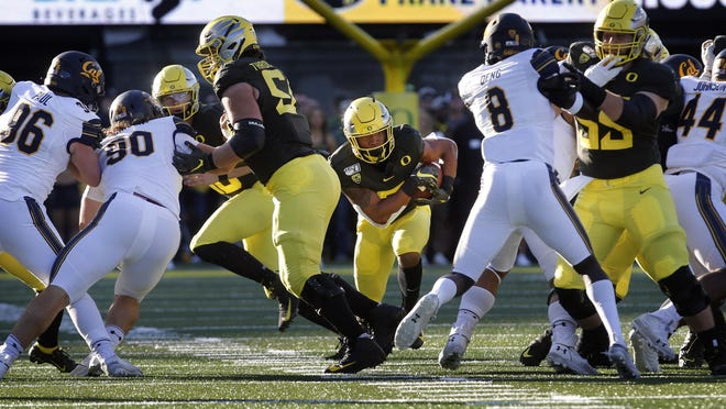 Oregon running back CJ Verdell runs through a hole during the first quarter of the Ducks' home win over California last season at Autzen Stadium. [Andy Nelson/The Register-Guard] - registerguard.com