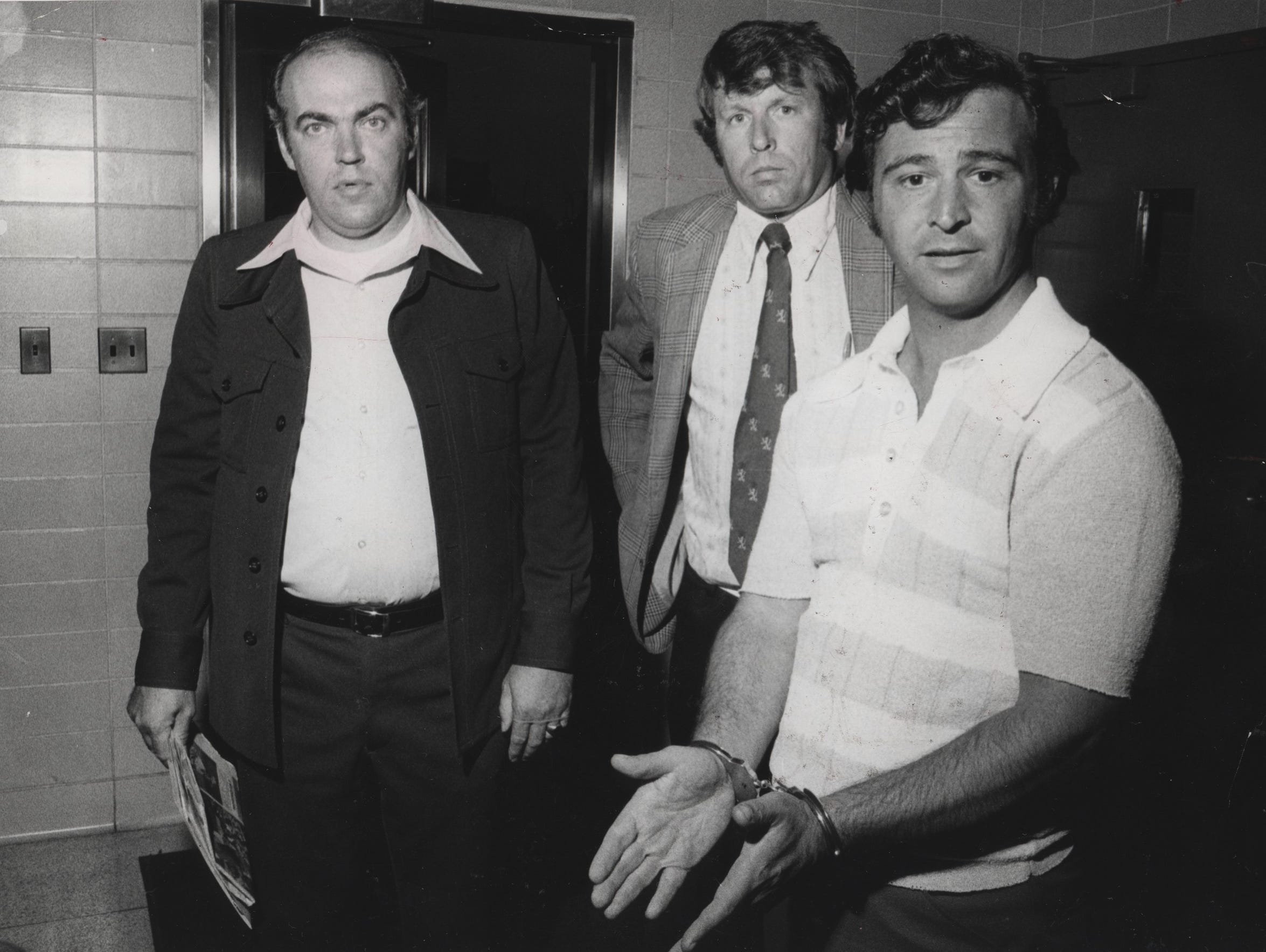 """Salvatore """"Sammy G"""" Gingello (in handcuffs) being taken into the Monroe County Jail in June 1975, after he had been linked to the 1973 murder of Jimmy """"The Hammer"""" Massaro. Gingello  was freed after it was determined that police had fabricated some of the evidence against him and others."""