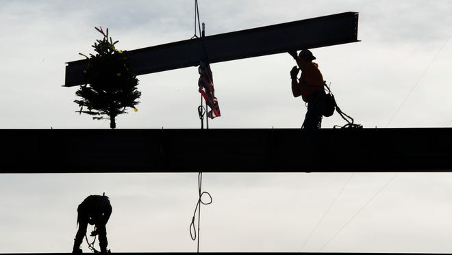 Construction workers move the top beam into place in a $102 million dollar expansion to Poudre Valley Hospital on Friday in Fort Collins. The project will include new space for emergency services and a helicopter pad.