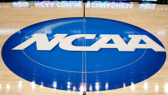 In this March 18, 2015, file photo, the NCAA logo is at center court as work continues at The Consol Energy Center in Pittsburgh, for the NCAA college basketball second and third round games. A federal judge in Chicago gave preliminary approval Tuesday, Jan. 26, 2016, to a reworked head-injury settlement between thousands of former college athletes and the NCAA that includes a $70 million fund to test for brain trauma.