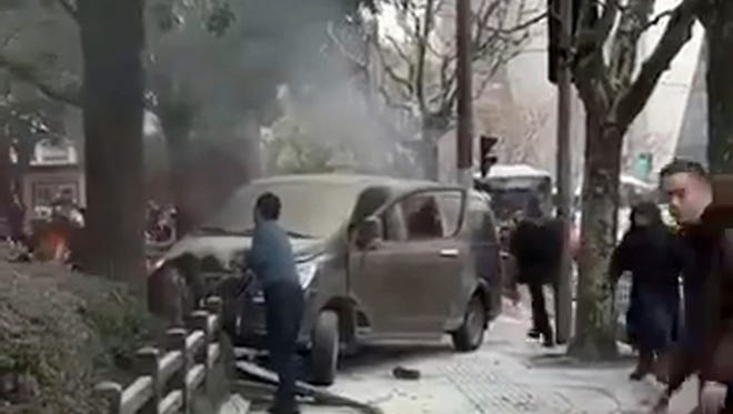 In this image, taken from cellphone video provided to the Associated Press, a minivan involved in an accident rests on the sidewalk along a street in Shanghai.