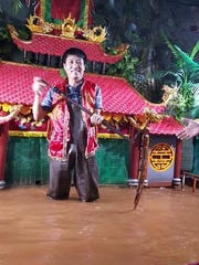 A puppet master displays a hand carved water puppet