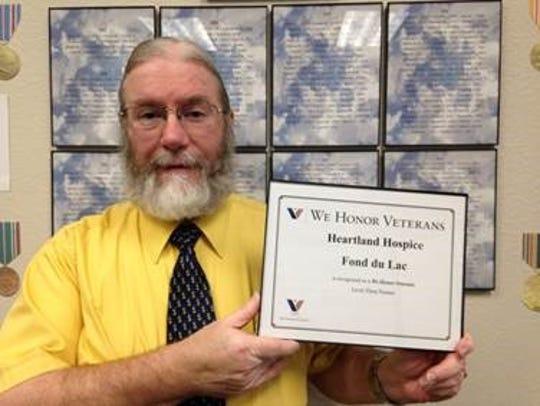 Bob Lantz poses with an award recently given to Heartland