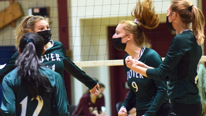 Members of the Dover High School volleyball team, including Morgan Raineri (9), celebrate a point during Thursday night's Division I match at Portsmouth.