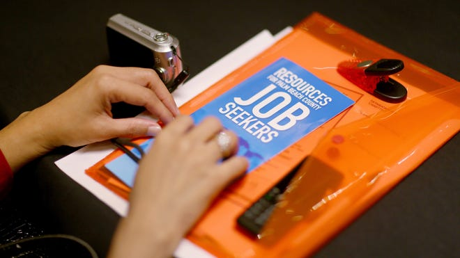 A job seeker holds employment papers as she attends the Choice Career Fair on Nov. 7, 2013,  in West Palm Beach, Fla.