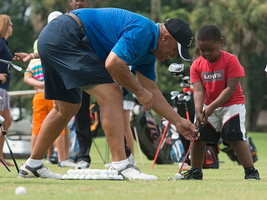 Golf Pro, Adrian Stills, left, helps Xavier Young,
