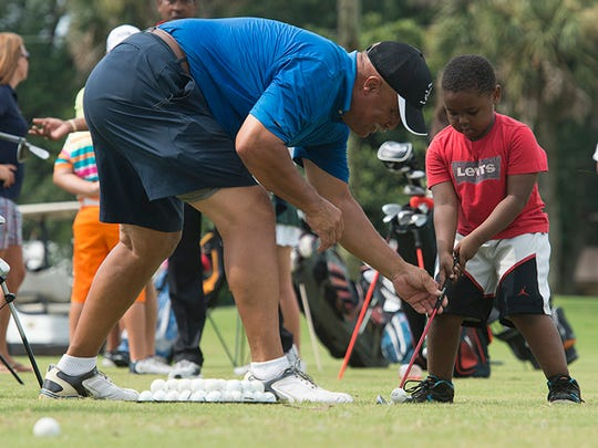 Golf Pro, Adrian Stills, left, helps Xavier Young, 5, learn new golf skills during the 40th annual Par Four Golf Tournament and First Tee clinic event at Osceola Golf Course Friday morning June 26, 2015.