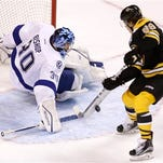 Tampa Bay Lightning goalie Ben Bishop (30) makes a stick-save on a shot by Boston Bruins right wing David Pastrnak (88) during overtime in Boston Thursday.