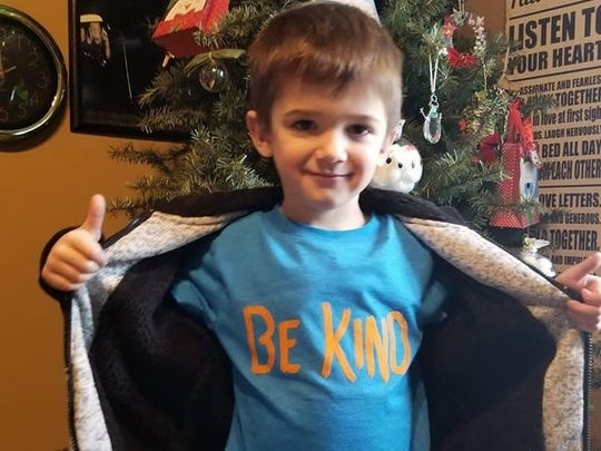 "Bentley Scheer, 4, shows off his ""Be Kind"" T-shirt. The youth helps clean up his neighborhood, with his dad, Nathan Scheer."