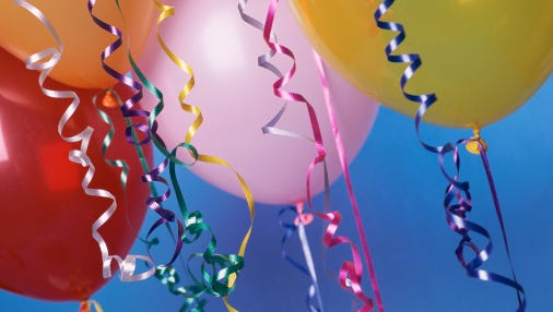 A stock image of balloons and ribbons.