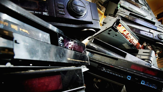 A pile of dusty and obsolete VCRs lies abandoned in a back room of a video repair shop in November 2004 in London.