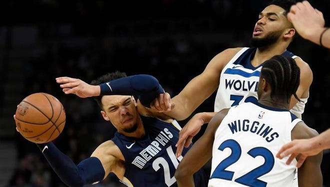 Memphis Grizzlies' Dillon Brooks (24) passes away from Minnesota Timberwolves' Karl-Anthony Towns (32) and Andrew Wiggins (22) during the third quarter of an NBA basketball game on Monday, March 26, 2018, in Minneapolis. The Grizzlies won 101-93.